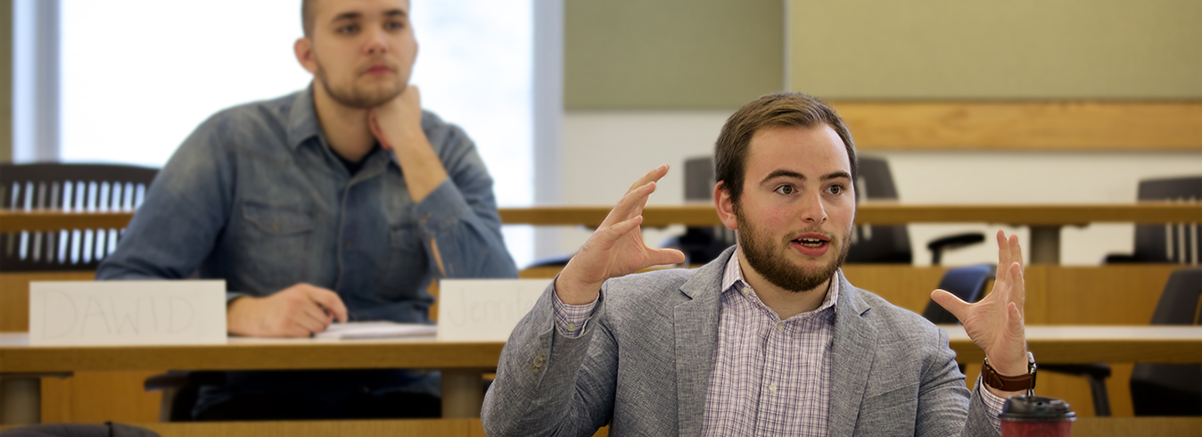 Male student gesturing with hands to answer a question in class