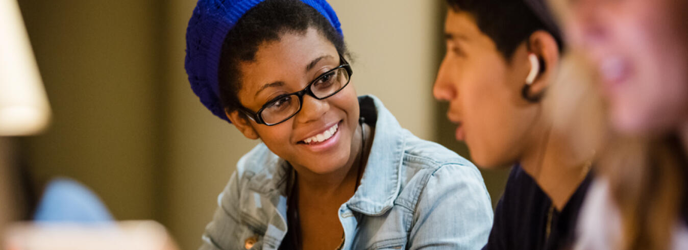 Female university student with blue hat and glasses talking with fellow classmates