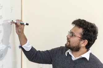 A professor stands before his class at a whiteboard.