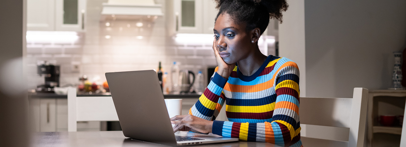 Female student studying on a laptop in her kitchen