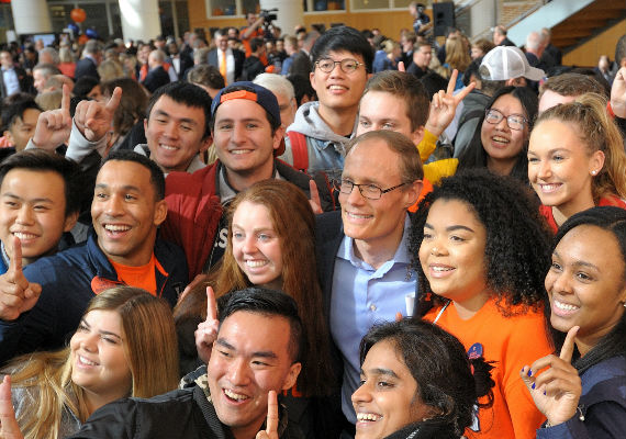 Larry Gies surrounded by students at the College's naming ceremony.