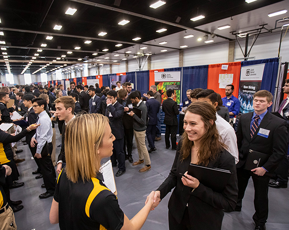 Student shaking hand with recruiter at business career fair